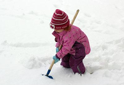 Ein Kind beim Schnee räumen